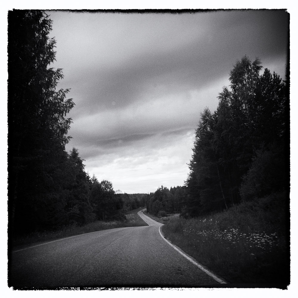 black and white view down a small country road in Finland with storm clouds above