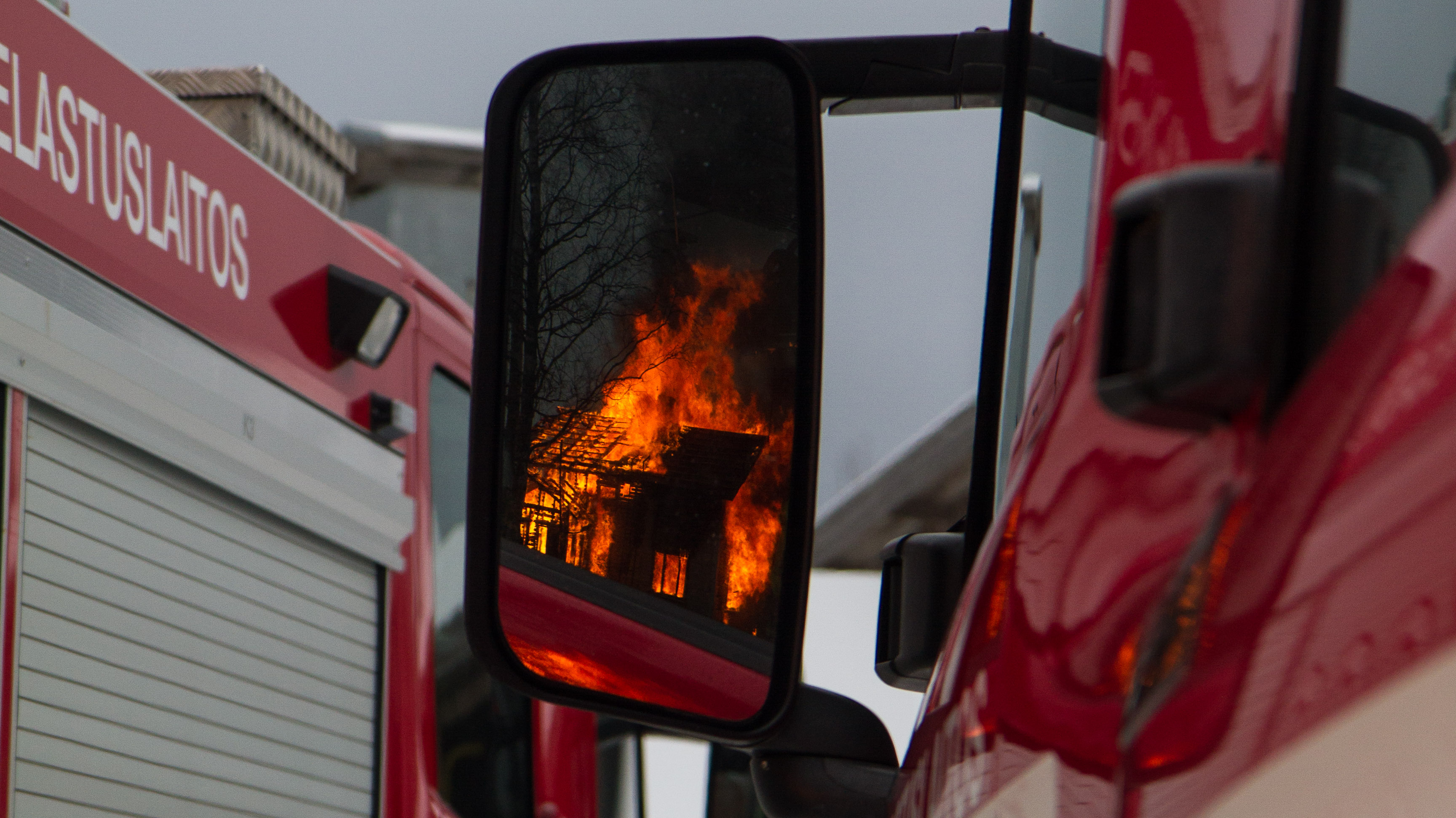 two firetruck and the reflection of a house fire